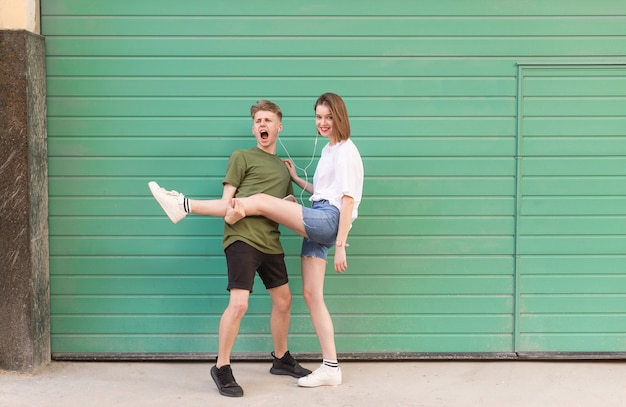 Funny couple of guys and girls standing against the of green walls and have fun