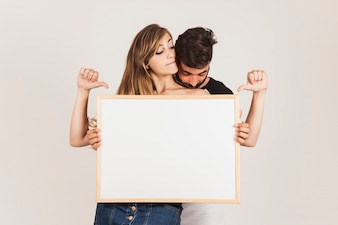 Funny couple holding board