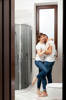 Funny couple kissing in bathroom