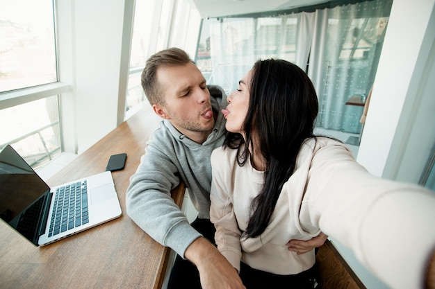 Funny couple makes crazy faces and takes photo. man and woman shows tongues to each other. strong relationship concept. funny jokes. woman holding smartphone and taking selfie.