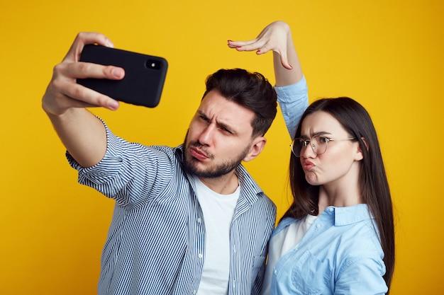 面白いカップルが顔をしかめると、黄色の壁越しにスマートフォンで自撮りをする