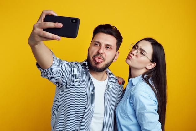 Смешная пара делает гримасу и делает селфи на смартфоне над желтой стеной