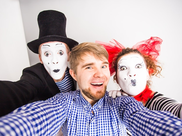 Funny couple of mimes taking a selfie photo.