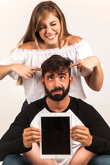 Funny couple showing tablet