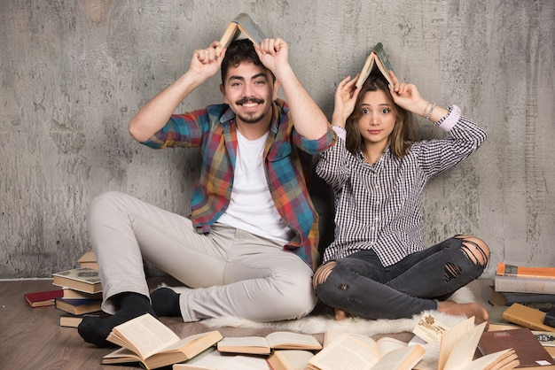 Funny couple sitting on the floor and holding books overhead