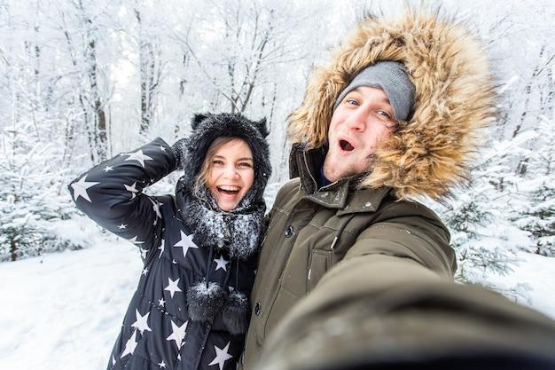 Смешная пара, делающая селфи зимой