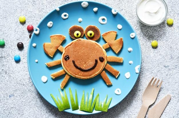 접시에 재미있는 게. 팬케이크 크랩, 어린이 조식.