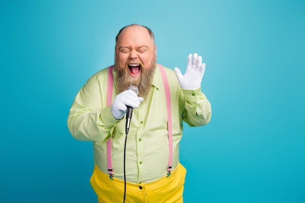 파란색 배경에 마이크에 노래 재미 미친 뚱뚱한 남자