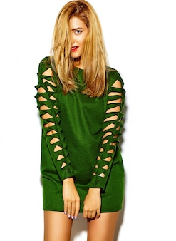 面白いクレイジーグラマースタイリッシュなセクシーな笑みを浮かべて美しい金髪の若い女性モデルのスタジオで緑の流行に敏感な服