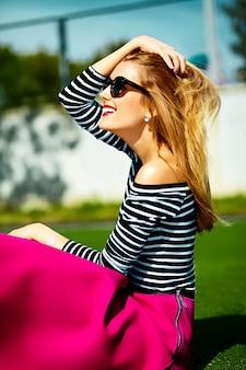 재미 미친 매력 세련된 섹시 공원에서 잔디에 앉아 분홍색 힙 스터 옷을 입고 아름다운 금발의 젊은 여자 모델