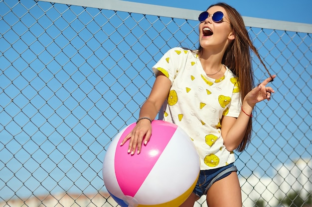 Funny crazy glamor stylish smiling beautiful young woman model in bright hipster summer casual clothes posing in the street behind iron grating and blue sky. playing with colorful inflatable ball floa