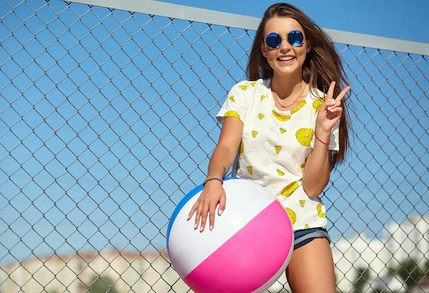재미 미친 미친 세련 된 웃는 아름 다운 젊은 여자 모델 밝은 hipster 여름 캐주얼 옷 철 격자 및 푸른 하늘 뒤에 거리에서 포즈. 다채로운 팽창 식 공 floa로 노는