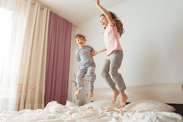 おかしいクレイジー。 2人の子供が寝室の大きなベッドで逆さまにジャンプしている、子供は両親なしで家にいる、実際のインテリアで本物のライフスタイル