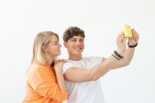 面白いクレイジーな若いカップルのブロンドの女の子と白い壁にポーズをとってヴィンテージの黄色いフィルムカメラで自分撮りをしている流行に敏感な男。写真の趣味の概念。