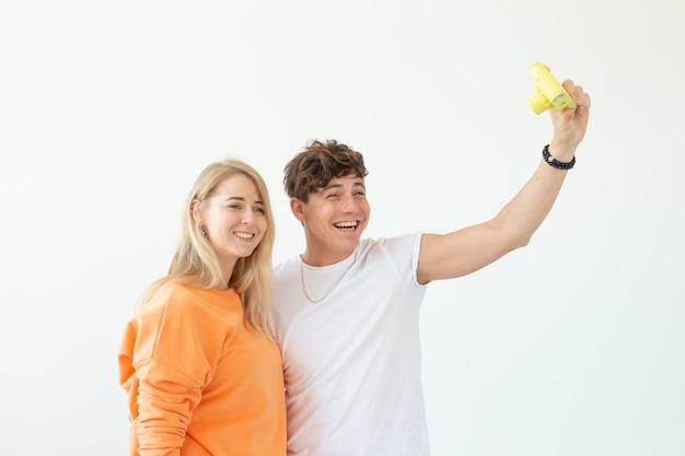 재미있는 미친 젊은 부부 금발 소녀와 흰 벽에 포즈 빈티지 노란색 필름 카메라에 selfie를 복용 hipster 남자. 사진 취미의 개념.