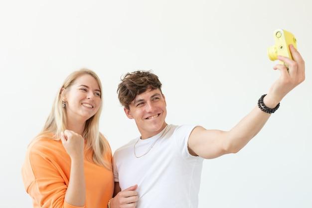 Смешная сумасшедшая молодая пара блондинка и хипстерский парень делают селфи на винтажном желтом фильме