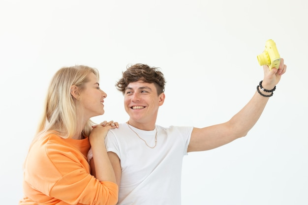 Funny crazy young couple blonde girl and a hipster guy taking a selfie on a vintage yellow film