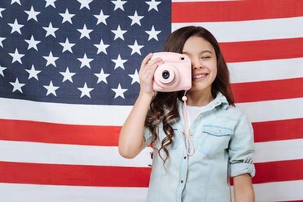Смешная творческая маленькая девочка веселится и выражает радость, стоя против американского флага и фотографируя