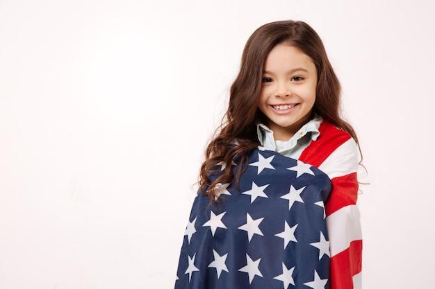 Смешная творческая улыбающаяся девушка веселится и выражает радость, стоя у белой стены и кладя флаг ей на плечи