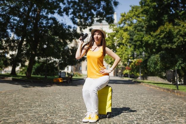 Funny curious traveler tourist woman in casual clothes, hat sitting on suitcase holding retro vintage photo camera in city outdoor. girl traveling abroad on weekend getaway. tourism journey lifestyle.