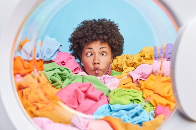 Funny curly afro american woman housekeeper crosses eyes makes fish lips poses with funny grimace drowned in heap of multicolored laundry has busy day washes clothes involved in housekeeping