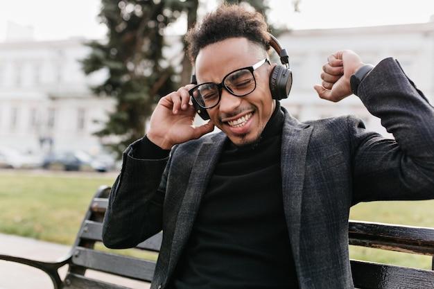 큰 헤드폰에서 재미있는 곱슬 흑인 듣는 음악. 벤치에 앉아 좋아하는 노래를 즐기는 우아한 재킷에 잘 생긴 아프리카 남자의 야외 초상화.
