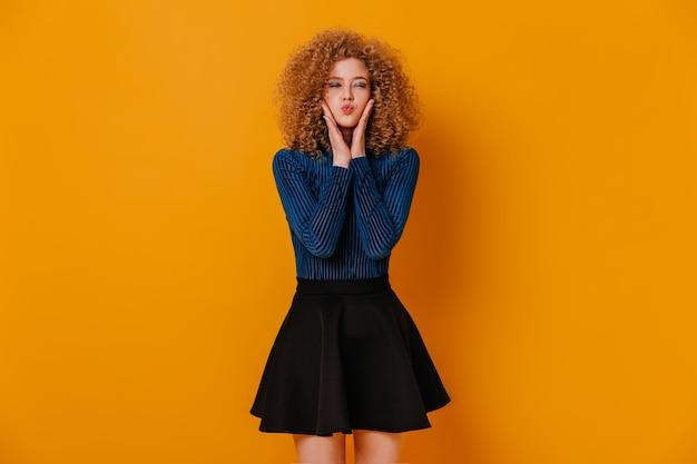 Забавная кудрявая девочка в синем свитере и черной юбке надула щеки на желтом пространстве.