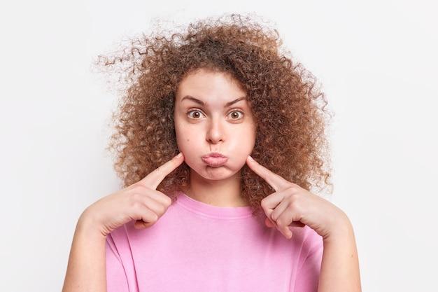 La donna europea dai capelli ricci divertente soffia le guance si diverte non perde mai il senso dell'umorismo trattiene il respiro fa una smorfia vestita con una maglietta di base isolata sul muro bianco. concetto di emozioni della gente