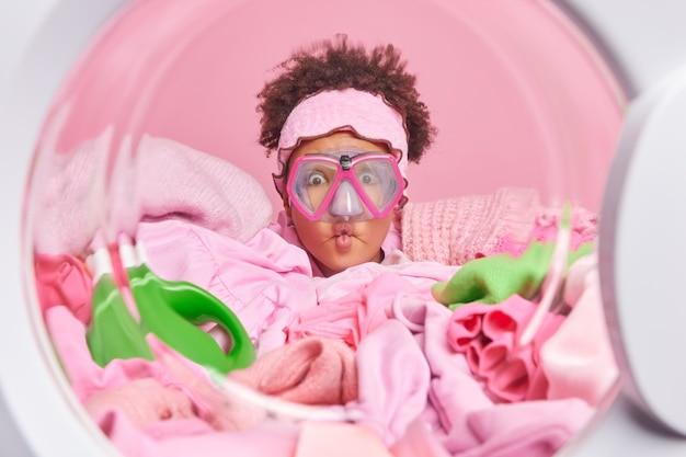 Divertente giovane donna dai capelli ricci fa una smorfia di labbra di pesce indossa la maschera per lo snorkeling pone dall'interno della lavatrice si prepara per il processo di riciclaggio circondato da un mucchio di vestiti sporchi da lavare
