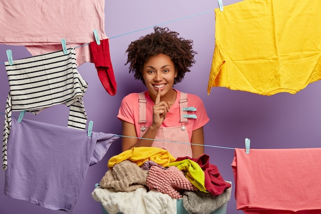 Funny curly housewife tells secret, smiles broadly, makes hush gesture, does washing at home, stands near pile of linen, hangs washed clothes on clothesline, isolated over purple background.