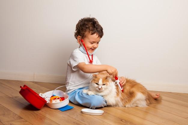 首に聴診器を持った医療用マスクと眼鏡をかけた面白い巻き毛の子供が猫と一緒に医者を演じる