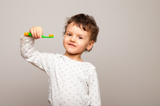 面白い巻き毛の子供は笑顔で立って、彼の手に歯ブラシを持っています。健康で強い子供の歯。個人衛生のルール。