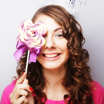 大きなロリポップを保持している面白い巻き毛の女性。誕生日会。