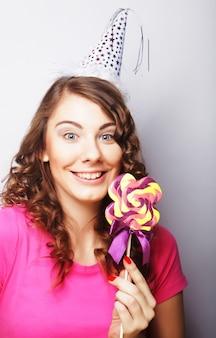 大きなロリポップを保持している面白い巻き毛の女性