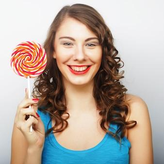 大きなロリポップを保持している面白い巻き毛の女性。
