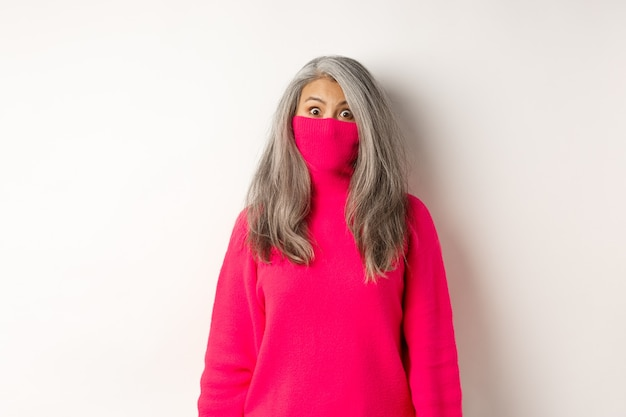 Funny and cute asian senior woman pull sweater collar on face and looking, standing on white.