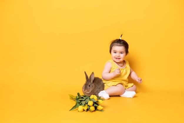 토끼와 튤립 노란색 배경에 앉아 노란색 드레스에 재미 있은 귀여운 아기 소녀.