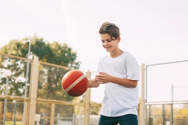 面白いかわいい男の子の運動選手はバスケットボールのゲームでボールをリードします。放課後、男の子がバスケットボールをする