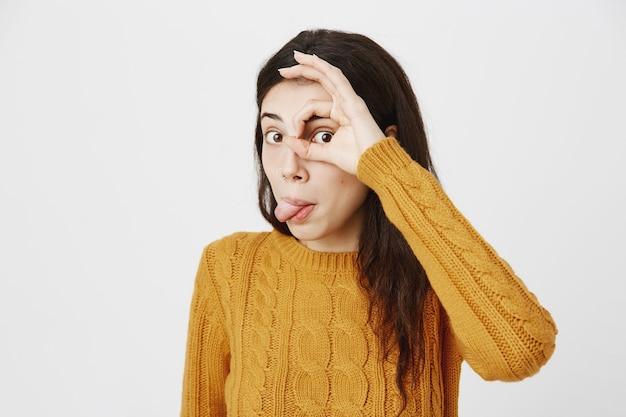 Ragazza bruna divertente e carina che mostra la lingua e fa il gesto giusto