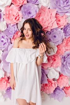 Divertente ragazza bruna carina che indossa un abito bianco al largo della spalla si trova in uno studio con sfondo di fiori rosa.