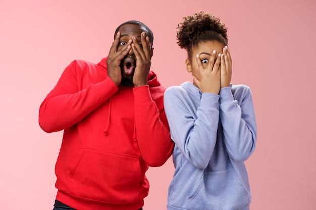 面白いかわいいのんきな愛情のあるアフリカ系アメリカ人のボーイフレンドのガールフレンドは、顔の手のひらを隠して、冗談を真似て指をのぞき、面白い真似をします。立っているピンクの背景は驚いています。