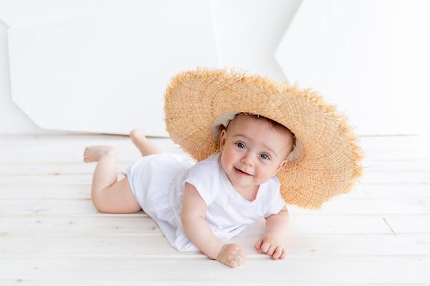 面白いかわいい子女の子3-4歳の白いトップとデニムのショートパンツを着て麦わら帽子を保持しています。幸福。夏のシーズン。