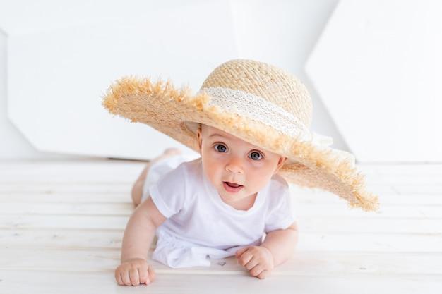 公園でポーズをとって白いトップとデニムのショートパンツを着て麦わら帽子を保持している面白いかわいい子の女の子3-4歳。幸福。夏のシーズン。