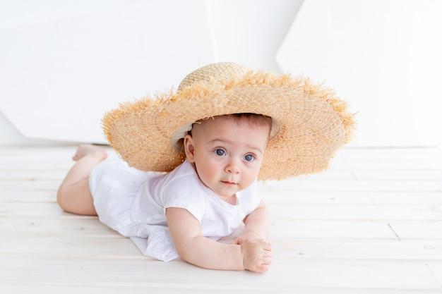公園でポーズをとって白いトップとデニムのショートパンツを着て麦わら帽子を保持している面白いかわいい子の女の子3-4歳