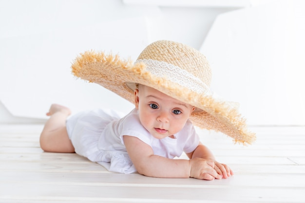 Funny cute child girl 3-4 year old holding straw hat wearing white top and denim shorts