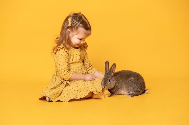 Смешная милая девочка ребенка в желтом платье с усаживанием кролика.