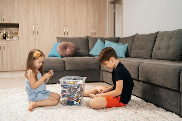 재미 있고 귀여운 소녀와 소년이 바닥에서 집에서 레고 놀이를 하고, 첫 번째 교육 역할 생활 방식