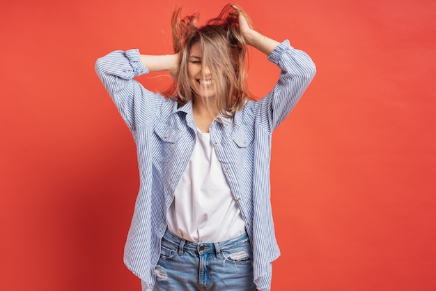 Funny, cute girl having fun while playing with hair isolated on a red wall