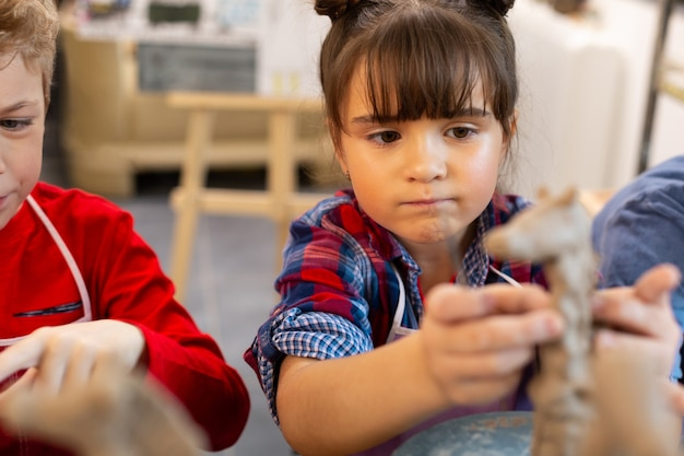 Funny cute girl modeling clay animals at art lesson