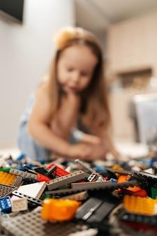 재미 있고 귀여운 소녀는 집에서 바닥에 레고를 하고 장난감에 집중합니다. 첫 번째 교육 역할 라이프 스타일